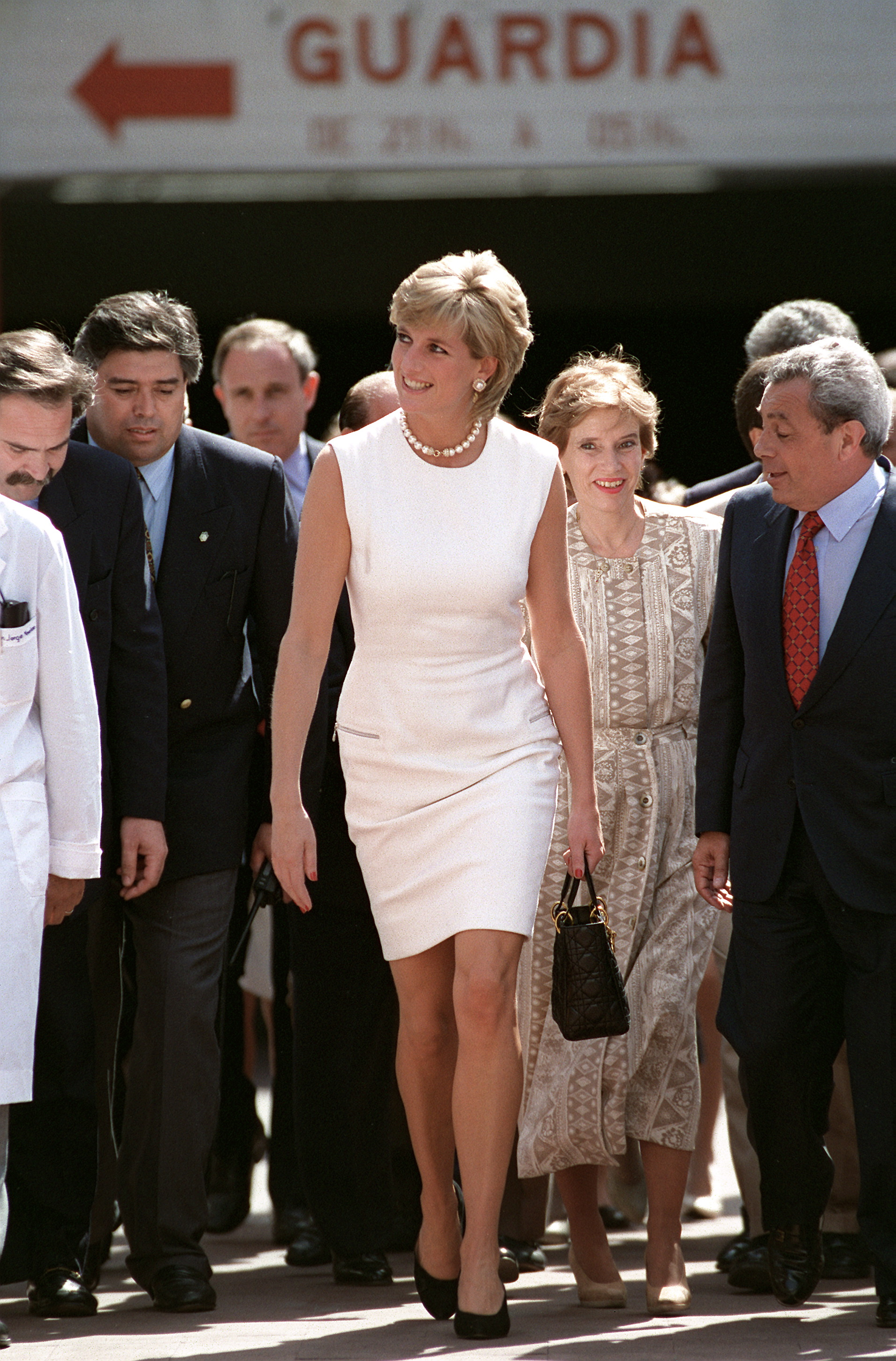 ARGENTINA - NOVEMBER 23: Diana, Princess Of Wales, Arrriving In Argentina. The Princess Is Wearing A White Sleeveless Shift Dress Designed By Fashon Designer Versace And Carrying A Black Christian Dior Handbag (Photo by Tim Graham/Getty Images)